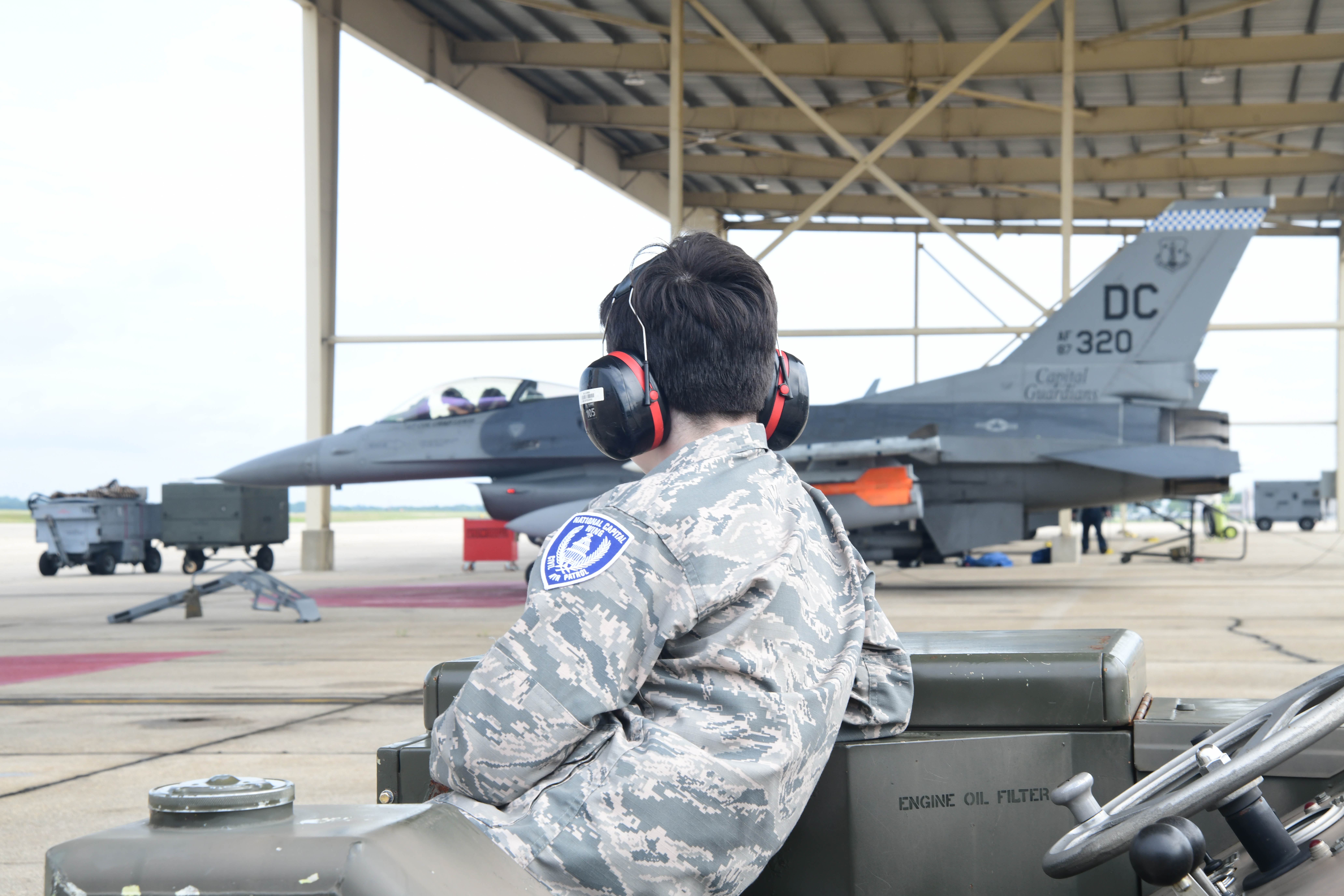 A cadet from Civil Air Patrol's National Capital Wing watches an F-16 Fighting Falcon being prepared for flight as part of a job shadow program.