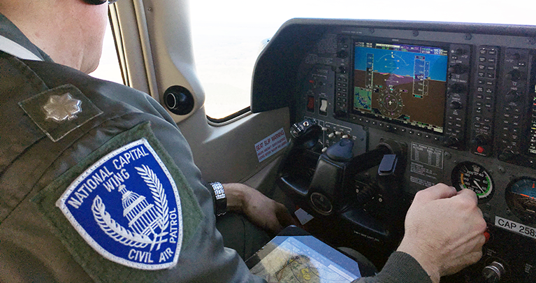A Civil Air Patrol pilot in the cockpit of a Cessna.