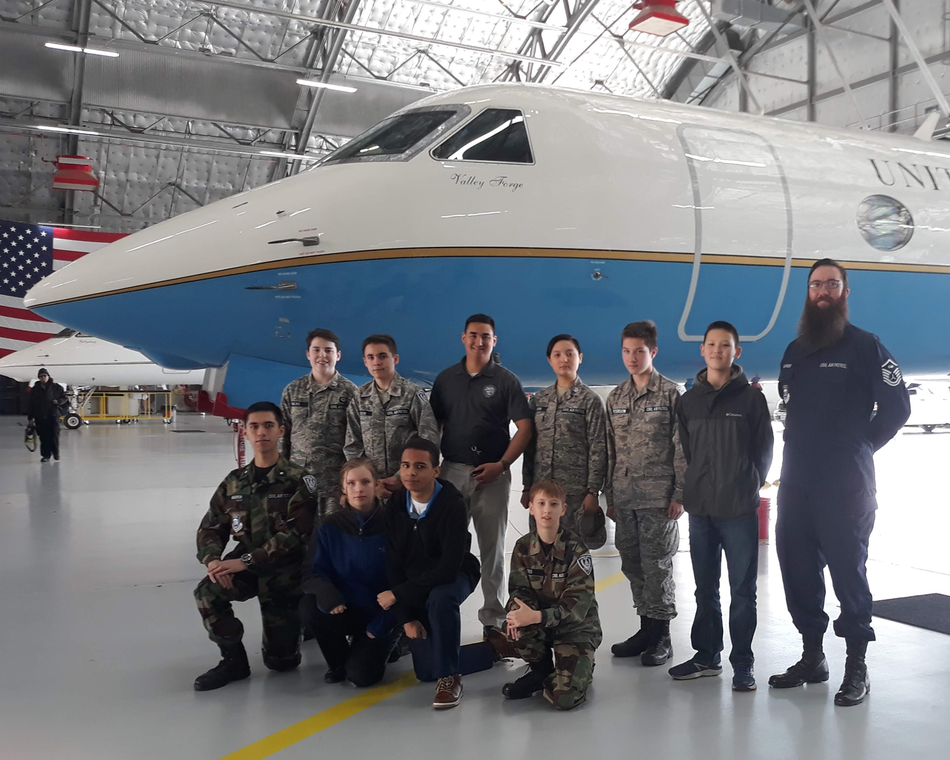 Members pose in front of an Air Force VIP aircraft.