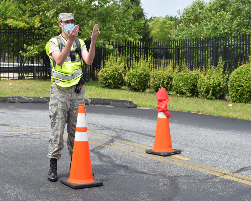 A cadet directs traffic at a COVID testing site.