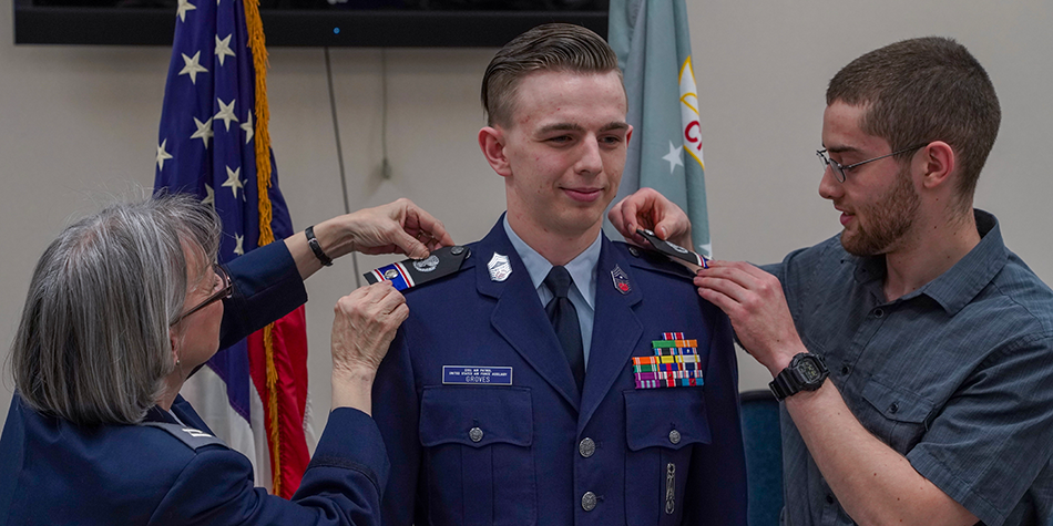 A cadet is promoted, and his family pins on the new cadet officer rank.